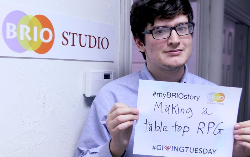 Billy Glazier photo holding up a sign 'Making a table top role playing game'